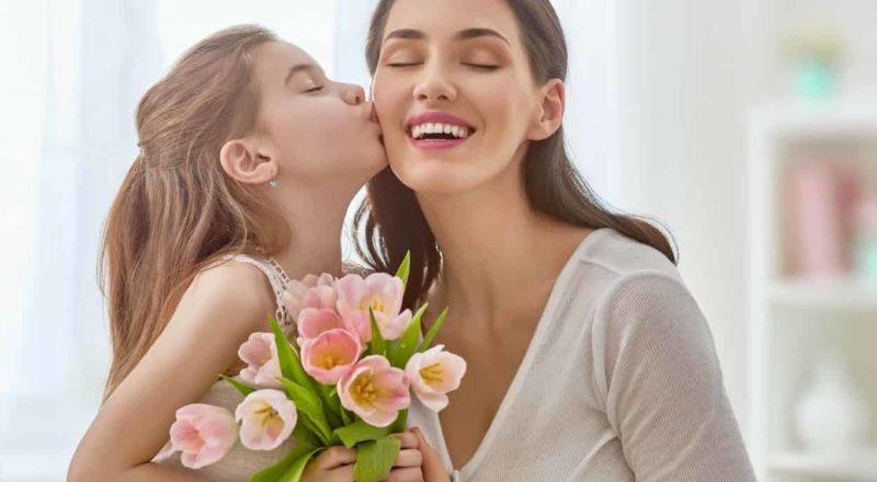 menina com flores cravo em mão beijando sua mãe